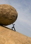 Businessman pushing large rock uphill --- Image by © John Lund/Blend Images/Corbis